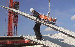 Der Cladboy VIAVAC kompakt CB-4Flex im Einsatz: Heben von Sandwichplatten zur Dachmontage.